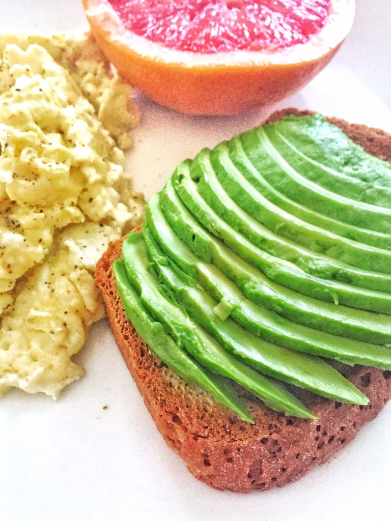 Avocado toast, scrambled eggs, and grapefruit - shot from a side angle